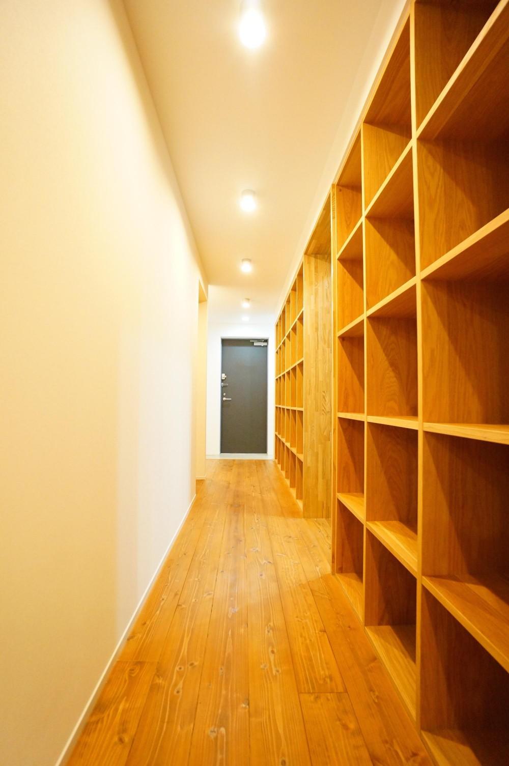 キッチンと一体化したテーブルが自然と家族を集わせる (圧巻の書棚がある廊下)