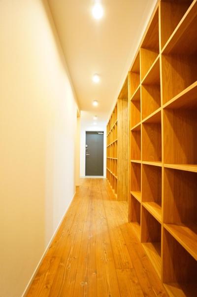 圧巻の書棚がある廊下 (キッチンと一体化したテーブルが自然と家族を集わせる)