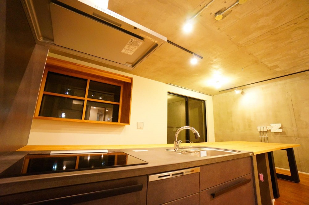 リビングに存在感のあるキッチン (キッチンと一体化したテーブルが自然と家族を集わせる)