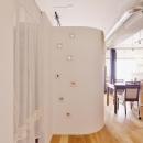 Y邸・漆喰の壁に囲まれて暮らす、光と風あふれる家の写真 カーテン内収納・R壁はリビングスペース