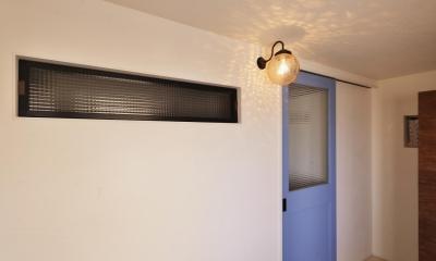 Y邸・漆喰の壁に囲まれて暮らす、光と風あふれる家 ((玄関土間から見た)室内窓と室内へ続くブルーの建具)