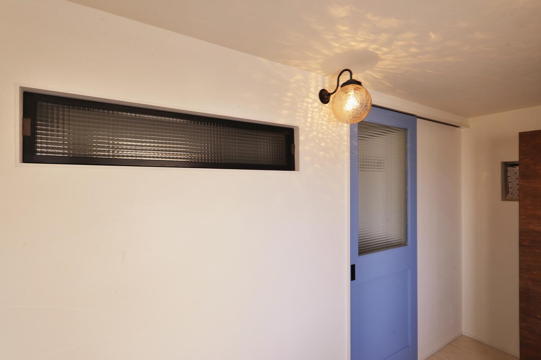 Y邸・漆喰の壁に囲まれて暮らす、光と風あふれる家の部屋 (玄関土間から見た)室内窓と室内へ続くブルーの建具