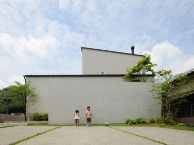 シンプルな白い外壁と煙突のある外観 (ゴトオリの家)
