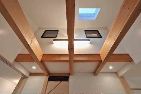海野の家の部屋 天窓と梁の見えるリビングを見上げる
