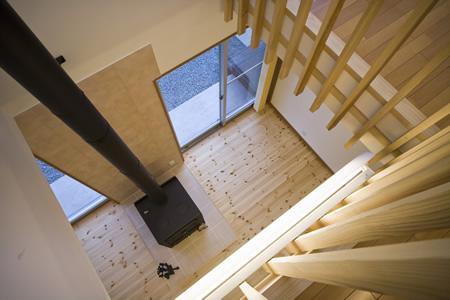 津市のA邸の部屋 吹き抜けから薪ストーブのあるリビングを見下ろす