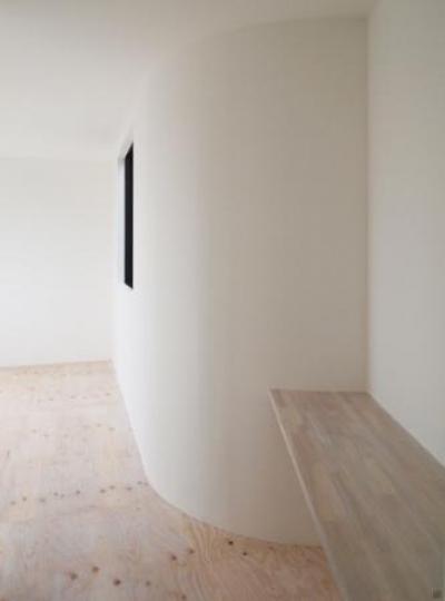 白い曲線の壁とカウンターのある寝室 (日野町のいえ)