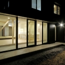 新田の家の写真 中庭から明かりのともったLDKと建物外観を望む