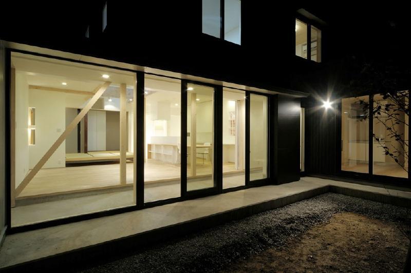 新田の家 (中庭から明かりのともったLDKと建物外観を望む)