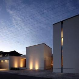 月栖の家(つきすみのいえ)~プライバシーと街並みの両立~ (明かりの灯った白いキューブ型の建物外観)