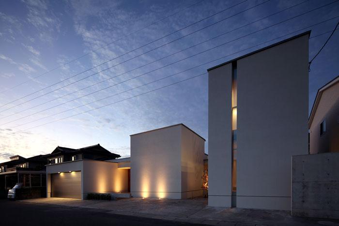 月栖の家の部屋 明かりの灯った白いキューブ型の建物外観