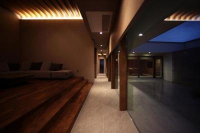 明かりの灯ったリビング・廊下 (月栖の家(つきすみのいえ)~プライバシーと街並みの両立~)