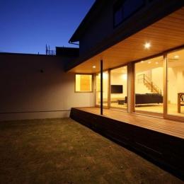 中庭から明かりの灯ったLDKと建物外観を望む