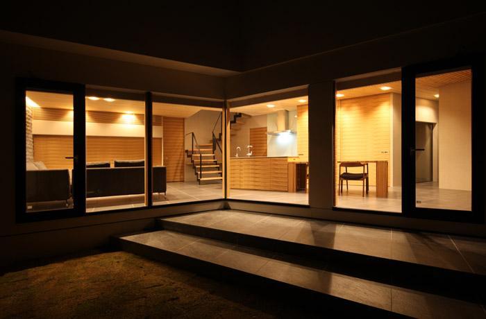 瀬石の家の部屋 中庭から明かりの灯ったLDKを望む
