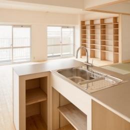 造作のオープンキッチンと本棚のあるLDK
