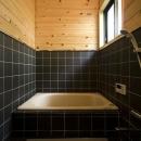 黒のタイルと水に強い天然材が使われた浴室