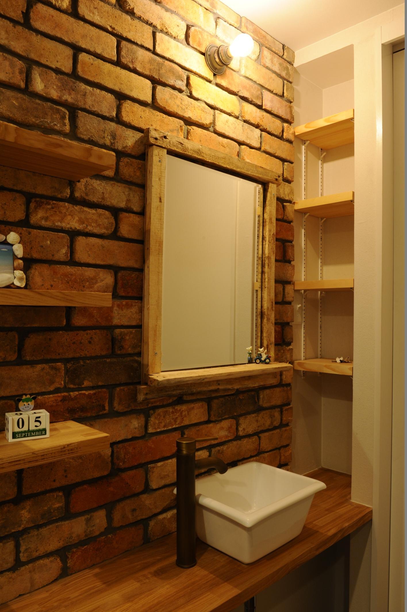 コドモゴヤの部屋 レンガの壁のある洗面エリア