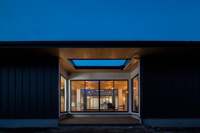 平屋・回廊の家の部屋 黒いガルバリウム鋼板の外観(夕景)