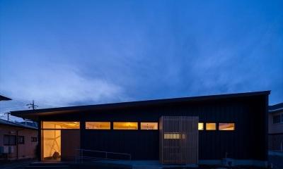 平屋・回廊の家 (黒いガルバリウム鋼板の外観(夕景))