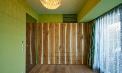 収納棚が印象的な緑色の壁の洋室|G-HOUSE