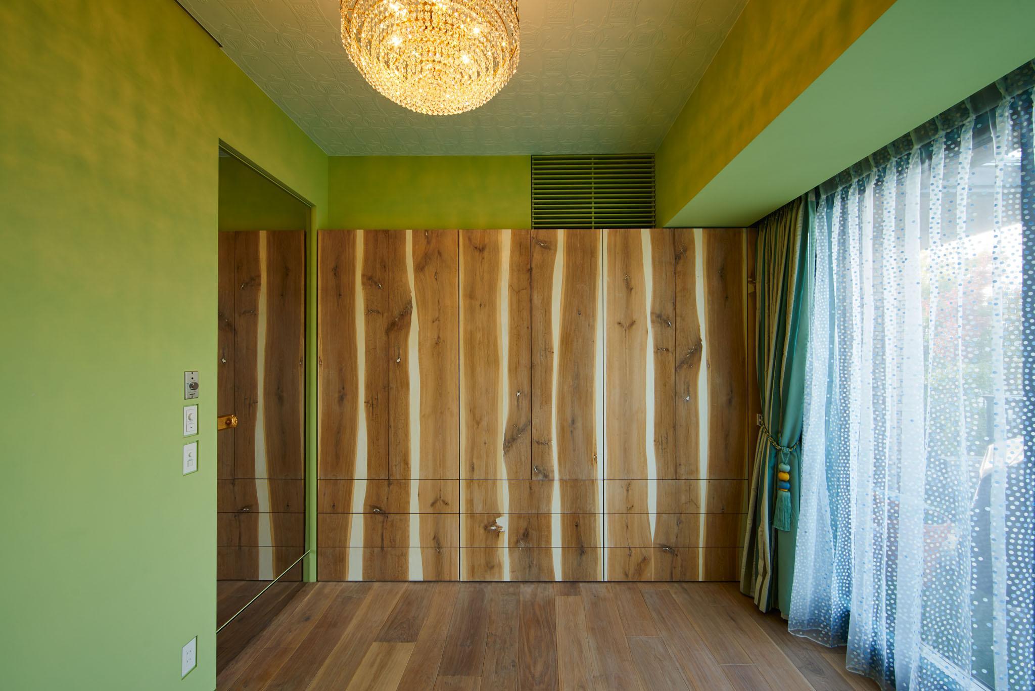 G-HOUSEの写真 収納棚が印象的な緑色の壁の洋室