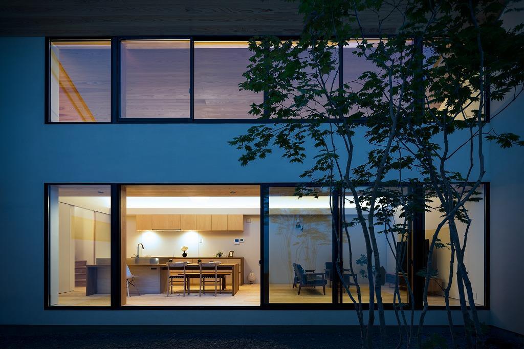 空を囲む家の写真 明かりの灯ったLDKを中庭から望む 2