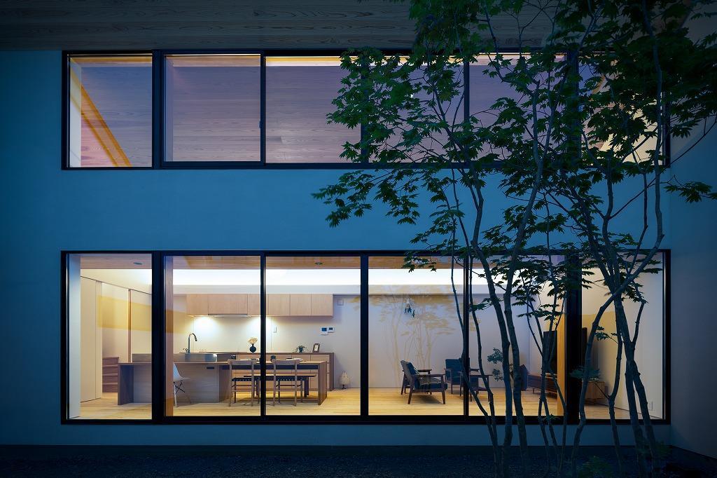空を囲む家の写真 明かりの灯ったLDKを中庭から望む 1