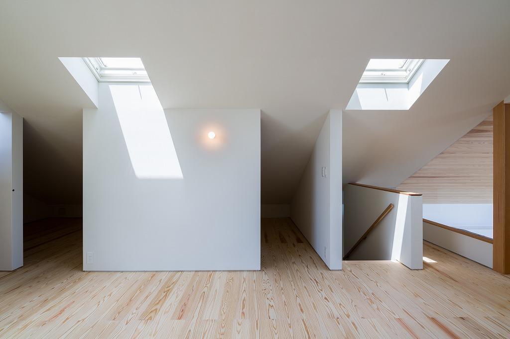 空を囲む家の写真 天窓と仕切り壁のある屋根裏 3