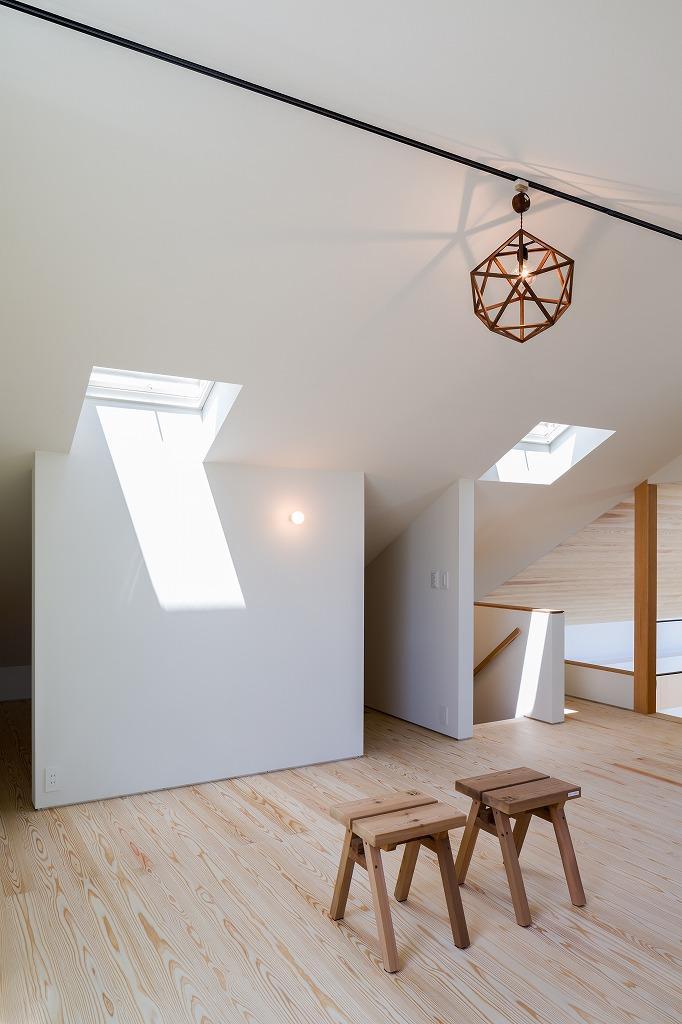 空を囲む家の写真 天窓と仕切り壁のある屋根裏 2