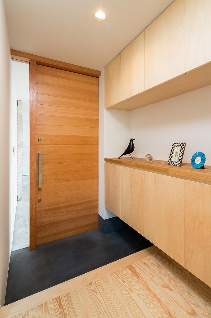 空を囲む家の写真 木製ドアと玄関