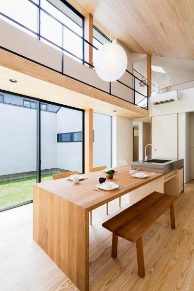 中庭が望めるダイニングテーブル付きアイランドキッチン (空を囲む家)