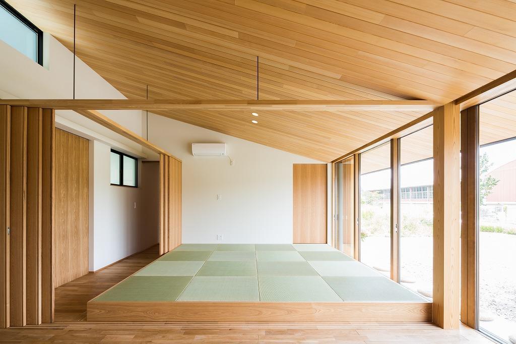 自然の恵みを感じる家の写真 琉球畳を敷いた畳スペースと間仕切り