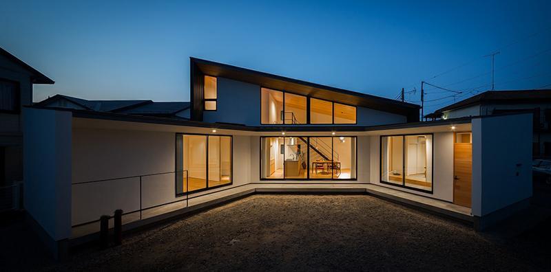 緩やかに囲む家の写真 明かりの灯った扇型外観 1