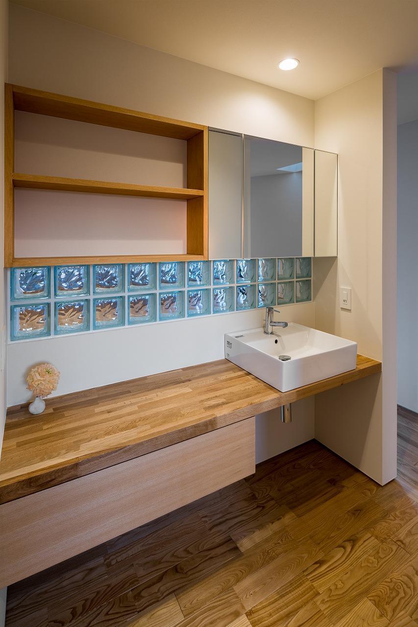 緩やかに囲む家の写真 青いガラスブロックのある洗面エリア