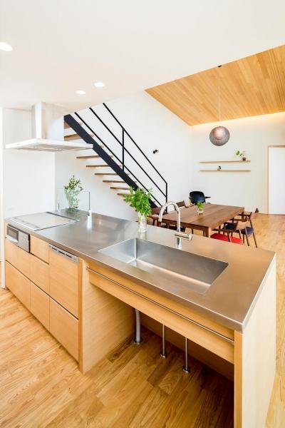 ステンレス天板のペニンシュラキッチン (緩やかに囲む家)