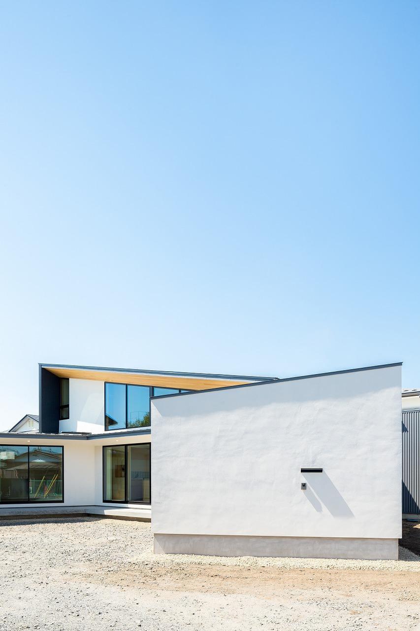 緩やかに囲む家の写真 扇型の白い外観