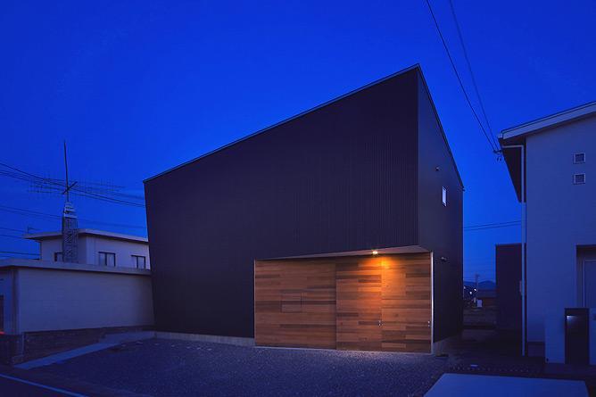 トンガリ壁の家の部屋 ビルトインガレージの黒い外観(夜景)