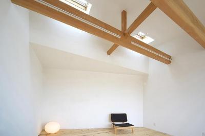 トンガリ壁の家 (高い天井と天窓からの採光溢れる部屋)