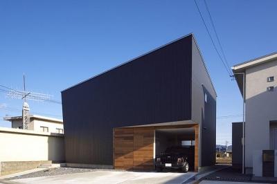トンガリ壁の家 (ビルトインガレージの黒い外観)