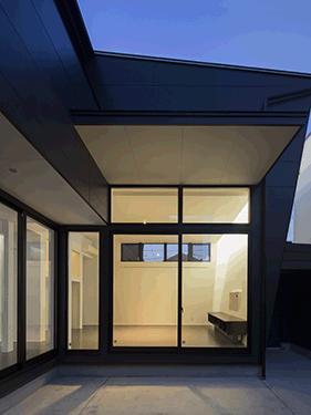 朝日の家 Ⅱの部屋 中庭から明かりの灯ったリビングを望む