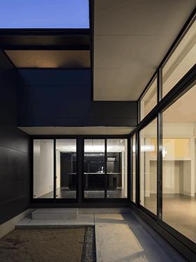 朝日の家 Ⅱの写真 中庭から明かりの灯ったLDKを望む