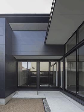 朝日の家 Ⅱの部屋 中庭からLDKと建物外観を望む