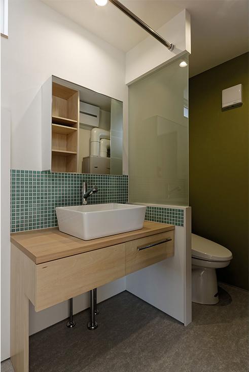 段差を繋ぐ家の部屋 モザイクタイルでアクセントされた洗面エリア