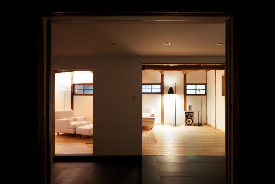 cow houseの部屋 梁の見える明かりの灯ったリビング 2