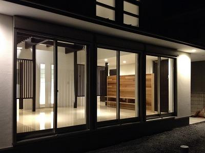 赤坂町の平屋~平屋を活かした高天井のある住まいの部屋 明かりの灯ったリビングを望む