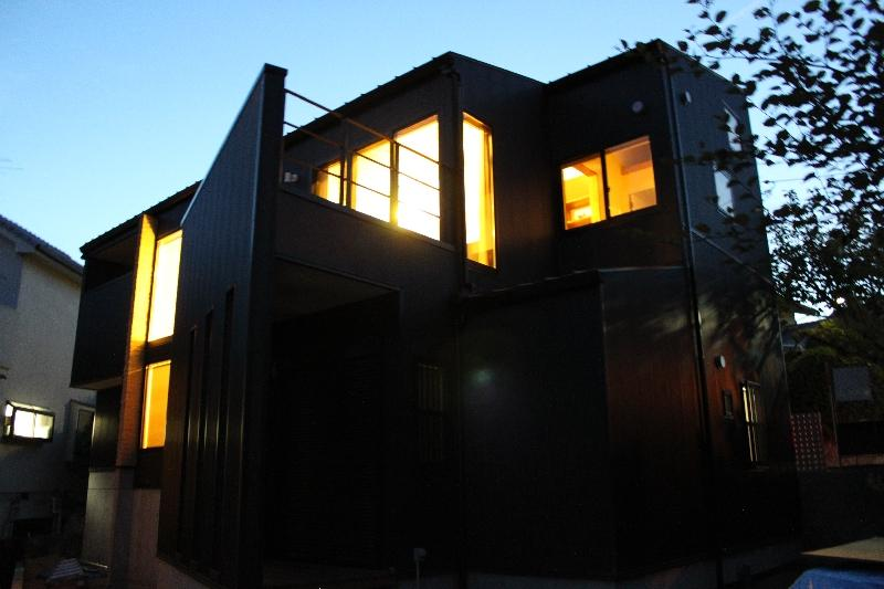 宝塚高台に建つリゾート住宅の部屋 明かりの灯った黒い外観