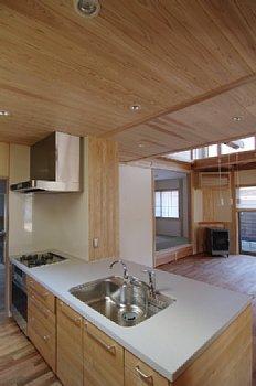小田原の家=神奈川県 海風が通り抜ける吹抜けと大黒柱の家の部屋 白い人工大理石のオープンカウンターキッチン