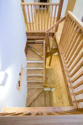 白壁と木の家 (2階から見下ろした階段吹き抜け)