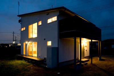 白壁と木の家の写真 バルコニーのある外観 (夜景)