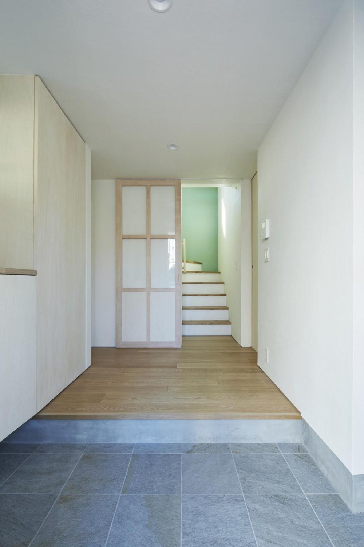 要町の家 吹抜けを通して光が溢れる家 (階段からの光が落ちる玄関)