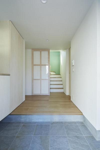 階段からの光が落ちる玄関 (要町の家 吹抜けを通して光が溢れる家)